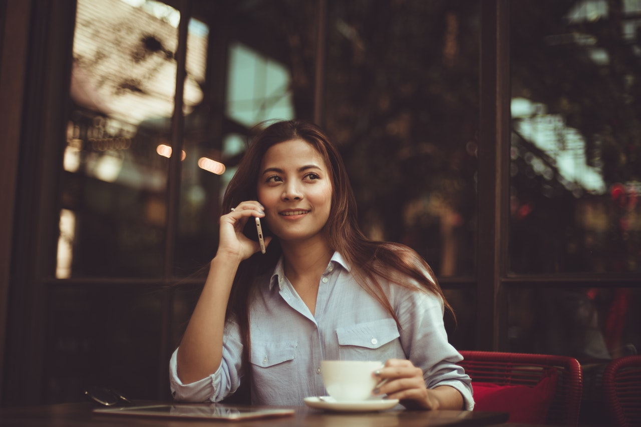 portrait-of-young-woman-using-mobile-phone-in-cafe-323503 (1)